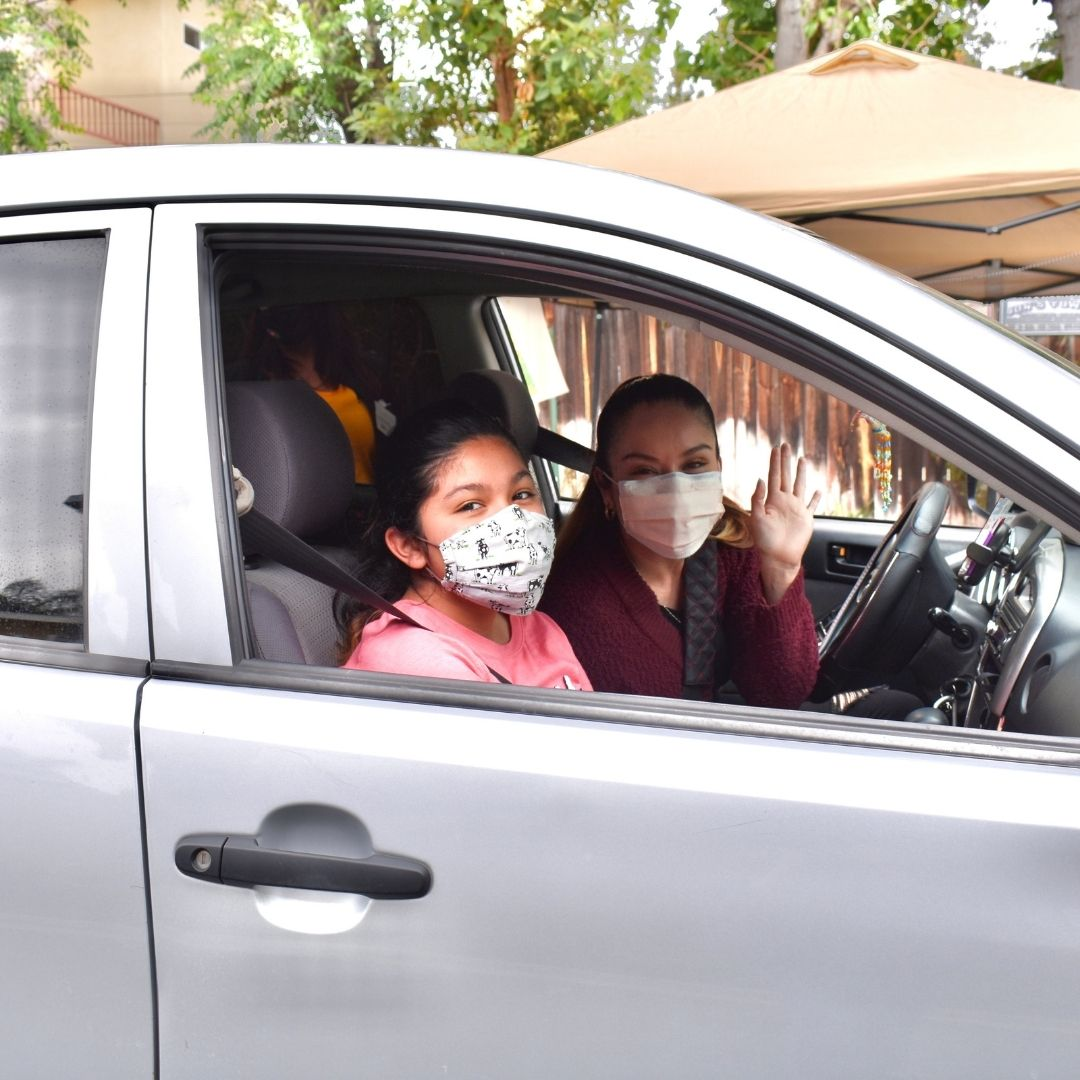 Mother and daughter in car waving