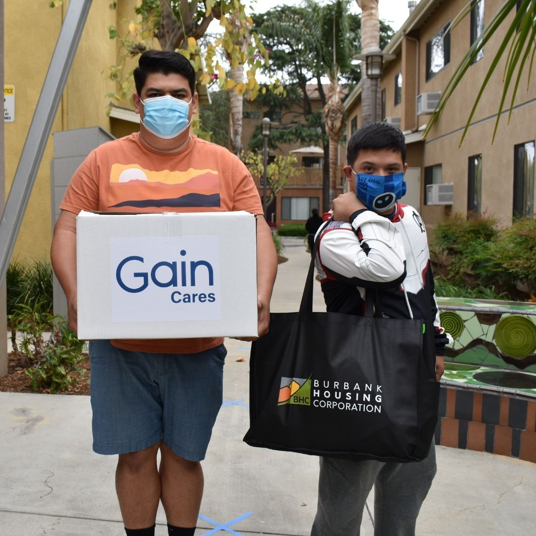 Two people, one holding a food packages with the writing Gain Cares and the other with a bag with the Burbank Housing Corporation logo